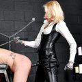 Mistress in leather dominates her slave with strap-on