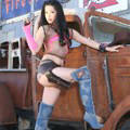 Babe in jeans boots with gun