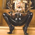 Susan Wayland in latex is posing on chair